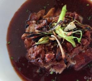 Pies de cerdo deshuesados con setas de temporada, ajos tiernos y reducción del jugo de cocción